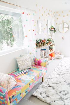 Colorful room with a colorful couch, a cozy rug, a dotted curtain and lots of golden dots on the walls.