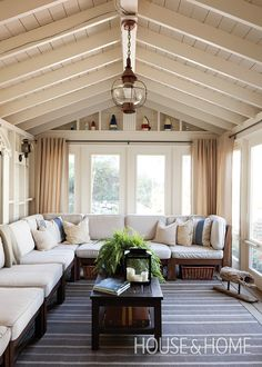 Subtle East Coast motifs, including weathered buoys and a bronzed pendant lantern, bring charm to this cottage sunroom.   Photographer: Janet Kimber   Designer: Philip Mitchell