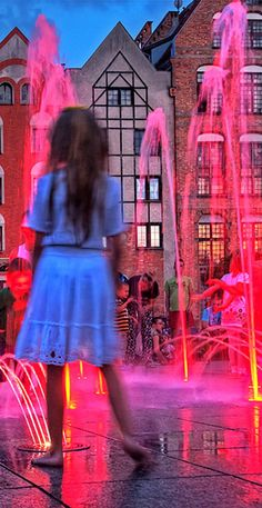 colorful fountains in the cathedral square in Elblag, Poland, Children are pleased, have a refreshment in hot days.