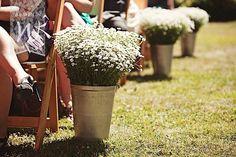 Semplicissimo ma romantico allestimento per un matrimonio stile country: vasi con mini santini bianchi