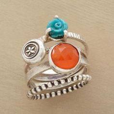 A bouquet of rose-carved turquoise, a stamped-sterling silver flower, carnelian and a beaded sterling silver band. Handmade for Sundance. Whole sizes 5 to 9. Set of 4