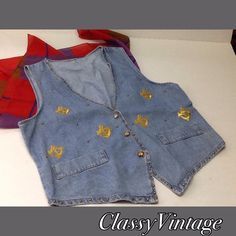 Vintage denim vest with a nautical theme. Vintage vest with gold embroidered anchors - gold tone buttons and outlined in gold tone studs. Faux pockets. No tags. Bust 40 and length 23 inches to longest point on front. Vintage Jackets & Coats Vests