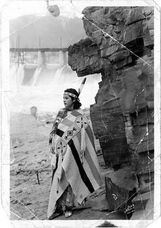 Native American woman, standing alone by cliff