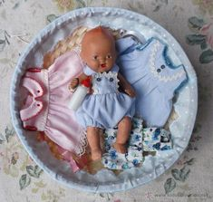 Simpática cesta con bebé español de piedra y cuatro vestiditos