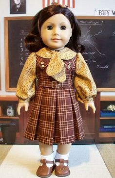 Brown hair bow with white ankle socks and chestnut brown t-strap shoes. Plaid dress with removable collar and buttons on top of each side, attached belt and long sleeves, pleated skirting. Burgundy and golden yellow plaid. Collar and sleeves ( golden yellow) School 1930's
