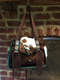 The Bonnie Bag with the owners brand in turquoise suede, hand cut suede  fringe and side pockets. All stitched up in turquoise leather lace.  gowestdesigns.us