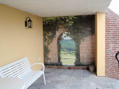 Op een fraaie manier heeft deze klant de een tuinposter als doorkijk gebruikt om een saaie stenen muur weg te werken!