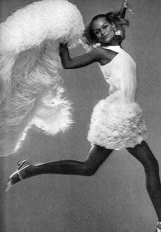 Lauren Hutton is wearing a snow-white crepe dress with rows of ostrich puffs by Geoffrey Beene, photo by Avedon, Vogue 1966
