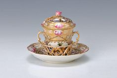 cup, KPM Berlin, around 1798, seascores in magenta and polychrome, rich painting in large and small cartridges encircling Panorama- landscapes with sailing ships, rich gold decoration, cup stand in fretwork, H.approx. 11.5 cm, gilding partially slightly abraded . German Description: Schokoladentasse, KPM Berlin, um 1798, Seeprospektszenen in purpur und polychrom, reiche Bemalung in grossen und kleine Reserven umlaufend Panorama- Landschaften mit Segelschiffen, reiche Goldornamentik…