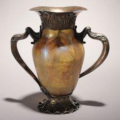 """Jarron """"Favrile Glass"""" montado sobre plata. El jarron de """"Favrile Glass"""" (un tipo de vidrio ideado por Louis Comfort Tiffany, patentado en 1894 y diferente de los demas cristales iridiscentes porque el color y el brillo esta no solo en la superficie sino tambien en su interior) tiene la inscripción AI514 L.C.T. Sobre la montura de plata tiene una altura total de 26,5 cms. Fue parte del efimero museo japones Louis C Tiffany Garden Museum, cerrado por miedo a ser destruido por algun terremoto…"""