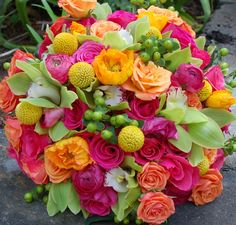 beautiful bright bouquet designed by tina barrera filled with billy balls, poppies, berries, ranunculus and orchids