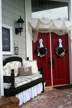 So much I love about this picture.  Chalkboard on porch, red doors, wondering about using burlap to decorate above the doors, etc.