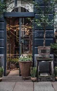 Lo que hace una preciosa puerta bien pintada,  acogedoras plantas, un gran cesto, mesas rusticas