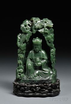 Jade Carving and Wood Stand, China, 19th/20th century, depicting a seated Buddha holding a bottle in his left hand, background with pine trees, bamboo, lingzhi and rocks, stone of dark green color with some dark markings, ht. 8 1/4 in