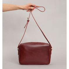 Claret Red Leather Felix Shoulder Bag: Medium claret red zip top shoulder bag made from the finest vegetable tanned leather. Unlined with one interior pocket and one exterior zip pocket.  Long buckled bridle leather strap 125cm.  Made in England.