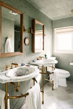 His and hers marble sinks in bathroom with tiled walls