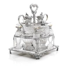 A George III silver eight-bottle cruet frame, Paul Storr, London, 1814 the square frame set on four scroll and acanthus feet, comprising four small cut-glass bottles with glass stoppers, two mustard pots and an oil and vinegar cruet, all cut-glass with with silver mounts, with two associated condiment spoons, G.W. Adams for Chawner & Co., London, 1853
