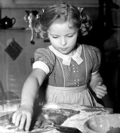Shirley Temple bakes a batch of cookies, 1938.