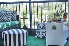 REVEAL // Viceroy Inspired Balcony Outdoor lanterns, outdoor love seats, green black and white stripe bamboo pattern outdoor throw pillows, outdoor ottoman, banana palm leaf print outdoor fabric, vintage brass pitcher, vintage cocktail glasses, HGTV Star, DIY, aloe plants, astro turf, high-rise pre-war, apartment building patio balcony terrace, outdoor entertaining, orange gold polka dot cocktail napkin, vintage equestrian ashtray, chihuahua