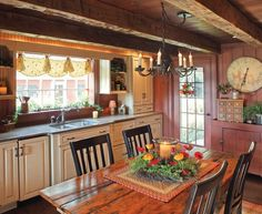 Living in Stark County, Ohio, Howard and Marsha Miller decided to construct a New England-style replica house that's a mix of old and new. Their solution in the kitchen is a galley of matched cabinets (albeit with traditional styling) along one wall, balanced by hewn beams, wide-board paneling, and antique flooring. Furniture is antique, and colors are of the period. The effect is seamless.
