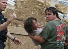 A child is carried from the rubble of the Plaza Towers Elementary School following a tornado in Moore, Okla.