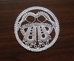 Znamení zvěrokruhu - blíženci Blíženci jsou paličkovaná krajka z bílé kordonetky vhodná k zarámování nebo do pasparty. Průměr znamení cca 13 cm.