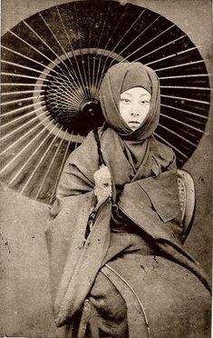 京都祗園の芸妓、江良加代。 御高祖頭巾を身につけた冬の装い。御高祖頭巾は宝暦(1751~1764)頃から明治時代にかけて流行した。 方形の布に耳をかける輪をつけており、耳にかけて顔を出す被り方と、目の周りだけ出す被り方がある。
