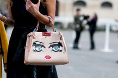 Chic Street Style From Paris Fashion Week  - Anna Dello Russo's quirky painted doll face handbag with neon orange piping and braided handles