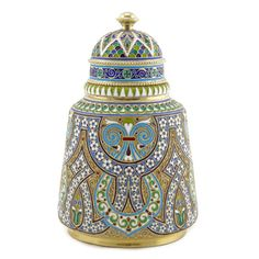 A Russian silvergilt and cloisonné enamel tea caddy, Antip Kuzmichev, Moscow, 1899-1908, retailed by Tiffany & Co. Enameled in an unusual amalgam of Neo-Byzantine and Central Asian architectural ornament combining a highly original adaption of the interlace decoration favored by Russian jewelers and silversmiths, the stippled gilt ground further embellished with fine, scrolling gilt wires, lid with multicolor fish scale ornament above a band of Neo-Byzantine crosses and beads.