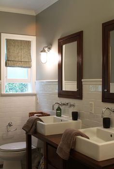 individual medicine cabinets built into wall...I like the separate sinks and wall mounted faucets.  Wrap-around tile gives a vintage look.