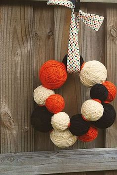 Halloween wreath Or use christmas colors for xmas. also instead of full yarn balls, could use halo yarn balls: yarn wrapped around balloons.