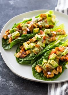Lettuce wraps filled with spicy taco-spiced chicken avocado tomato and drizzled with a zesty cilantro lime sauce. This healthy nutritious low-carb meal is a delicious protein packed option and great if you are on a low-carb paleo or keto diet! Lettuce Wrap Recipes, Chicken Lettuce Wraps, Avocado Chicken, Low Carb Tacos, Low Carb Meal, Keto Meal, 7 Keto, Salat Wraps, Cocina Light