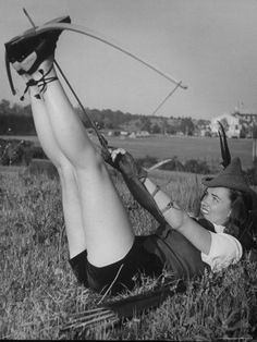 Actress Ella Raines with a bow and arrow C. 1940s