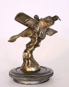 Avion signé B. F   Mascotte automobile  Signée B. F  En bronze argenté  Montée sur un bouchon de radiateur  Bon état   Hauteur : 12 cm - Largeur : 10 cm