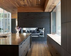 A brick fireplace divides a kitchen and living room.