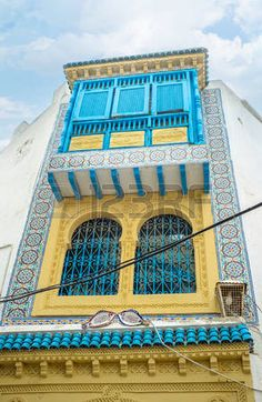 tunisia houses: HAMMAMET, TUNISIA - SEPTEMBER 6, 2015: The corner balcony decorated with the glazed tiles, carved wooden details and painted plaster, on September 6 in Hammamet.