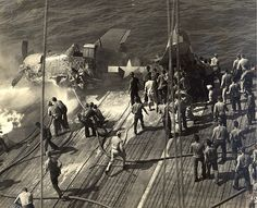 Fire control crews at work on a crashed F6F-5 Hellcat from Fighting Squadron 21 on the deck of USS Belleau Wood, October 6, 1943.