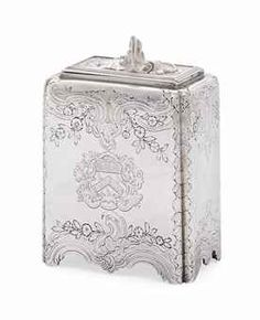 A GEORGE II SILVER TEA-CADDY MARK OF PAUL DE LAMERIE, LONDON, 1745 but mostly likely by an apprentice. Oblong, the sides chased with foliage scrolls, flowers and rocaille, the hinged cover with a rocaille, grotesque mask and shell finial, later engraved on each side with coat-of-arms, marked underneath 5 3/8 in