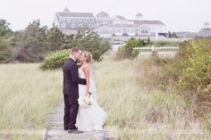 The bride and groom on a beach boardwalk with the Wychmere Beach Club behind them after their summer wedding in Harwich Port on Cape Cod... love this coastal venue and beach grass vibe!