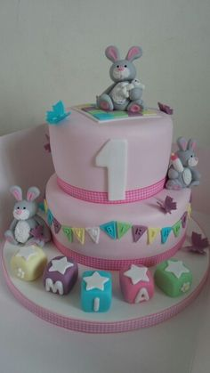 A beautiful pink 1st birthday cake complete with rabbits, bunting and building blocks. By Sarahs Cakes by Design.