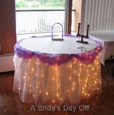 i kno purple isn't ur color, but i love the lights under the cloth. classy! nice cake table set up?