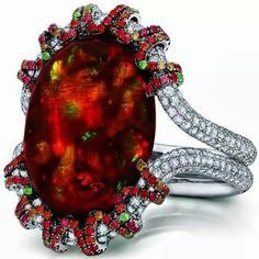 Martin Katz white gold ring featuring a central 13.18ct fire opal cabochon, micro-set with diamonds, tsavorite garnets and orange-red sapphires. #opalsaustralia