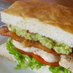 Pig Burger/The burger consists of: Grilled chicken fillet, grilled bacon, lettuce and tomato on a toasted foccacia bun, with herbed mayo on the base and guacamole on the crown./