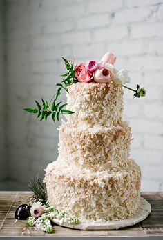 A coconut-covered three-tiered wedding cake with a fresh flower topper by @sugarbeesweets | Brides.com