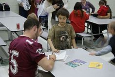 Veteran Racine Raiders quarterback Chris Walsh signs an autograph for a Julian Thomas Elementary School student as part of the Reading with the Raiders program.
