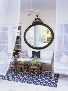 "Hang a Mirror:     This mirror makes the porch of a Florida home by designers Courtney Coleman and Bill Brockschmidt feel more like an actual room. An added benefit? ""At night it reflects the candlelight so beautifully,"" Coleman says. Smith & Hawken sofa; Madeline Weinrib carpet."