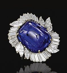SAPPHIRE AND DIAMOND RING. The sugar loaf cabochon sapphire weighing 29.96 carats, set within a border of radiating baguette and marquise-shaped diamonds, mounted in platinum, French assay marks.