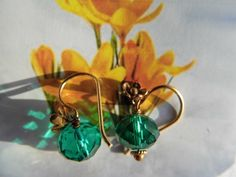 Øreringe med blomst i forgyldt sølv med dybgrøn swarowski sten designet til kvinden med den individuelle stil som ønsker at udvikle sig og favne verden. De grønne øreringe er gode til en smuk blomstret enkel sommerkjole fx i hvid eller en bluse med mange farver, hvor den grønne farve måske er med. De to øreringe danser tango med de gule forårsblomster. 175,00 kr. www.annweidesign.com