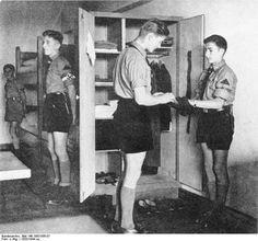 Hitler Youth leader inspecting the locker of other members, date unknown, pin by Paolo Marzioli