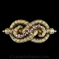 The curvilinear design of this antique lovers' knot also resembles a coiled double serpent - take your pick. This probably British-made jewel is rendered in highly textured 9 karat yellow gold with a deep, time-worn patina and brightened with five round g